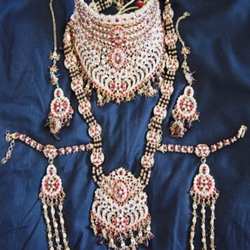 """Parure Mariée 1 - Ensemble 7 pièces comprenant : le collier """"ras du cou"""" avec pierres blanches et bordeaux, le long collier, les boucles d'oreilles, le bijoux de front (tikka) et la parure pour les mains."""