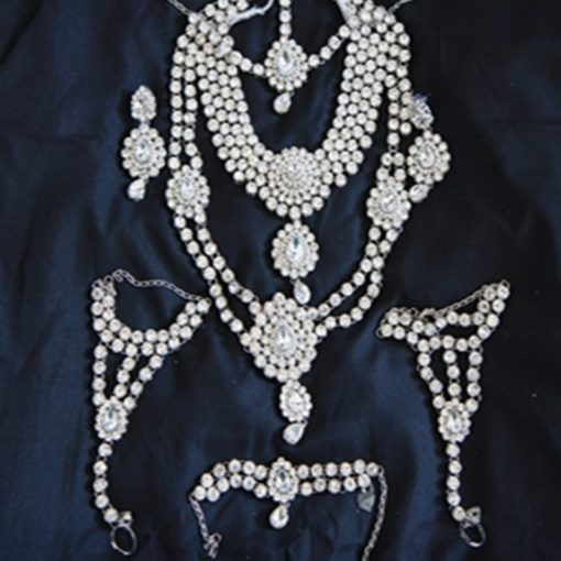 """Parure Mariée 2 - Ensemble 8 pièces comprenant : le collier """"ras du cou"""" avec pierres blanches, le long collier, les boucles d'oreilles, le bijoux de front, une parure """"mains"""" et le bracelet pour le bras."""